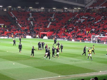 Premier League soccer players worth millions warming up at Old Trafford