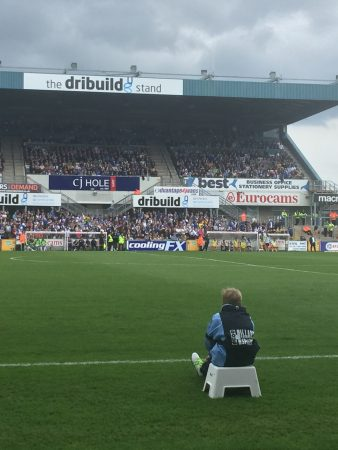 A ballboy watches from the sidelines at a Bristol Rovers soccer game.