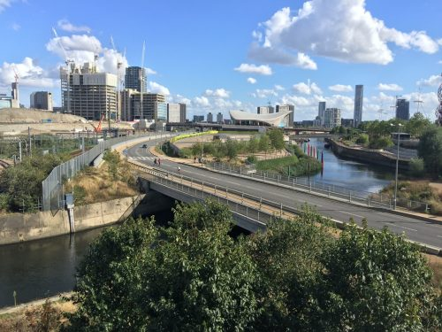 A road, canal and condos in the Docklands, London.
