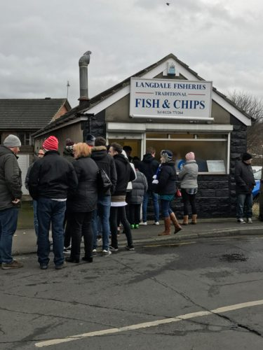 People waiting in line at Langdale Fish and Chips in Barnsley.