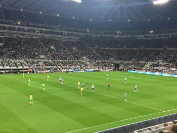 players on field fans in stands soccer stadium
