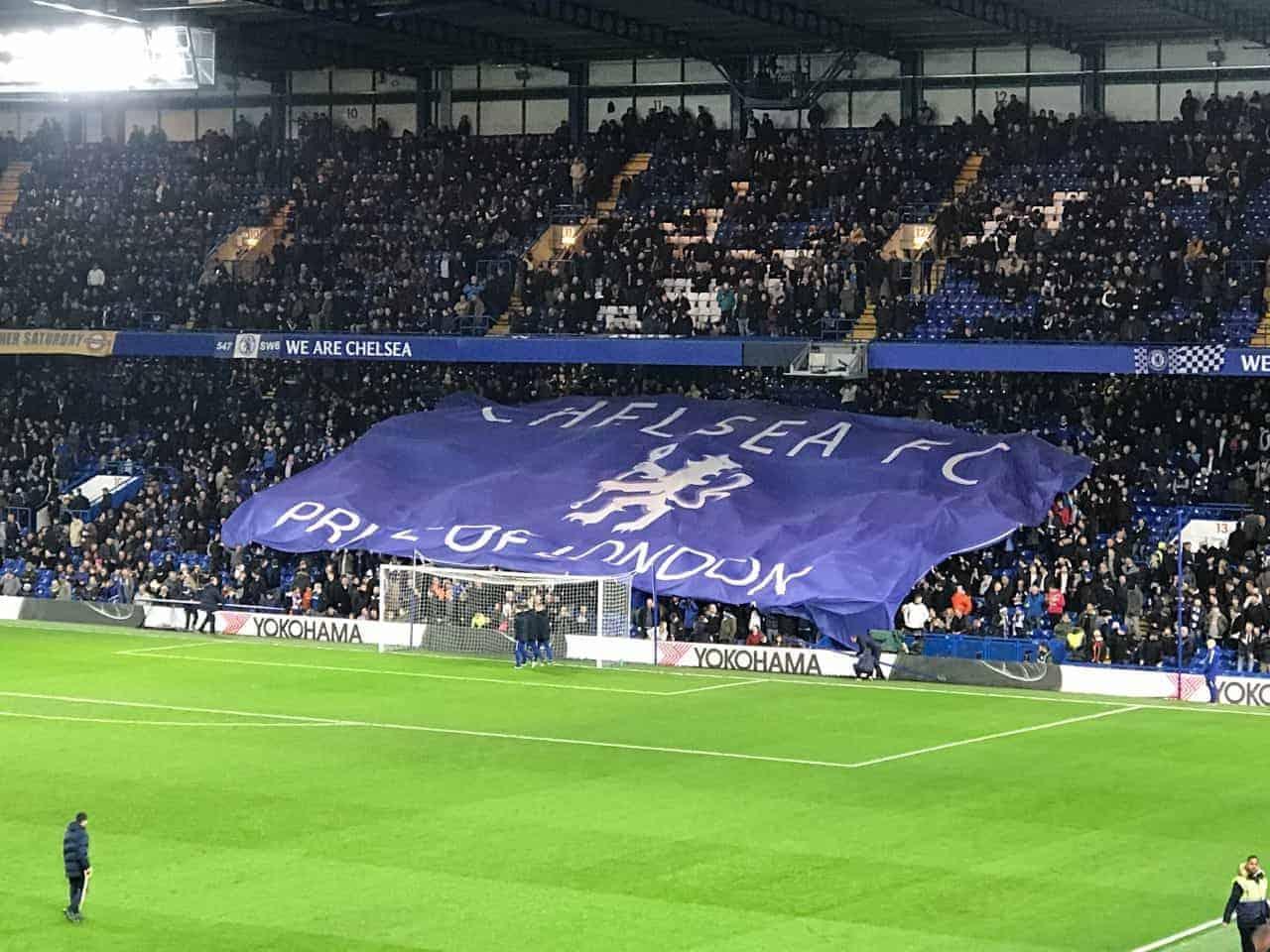 fans holding chelsea banner at stamford bridge