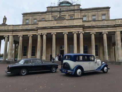 Fancy cars parked outside the Pump House with columns in Cheltenham.