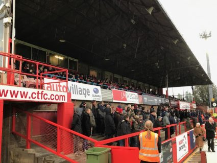 Supporters in the two-tier Main Stand at Whaddon Road, home of Cheltenham Town FC