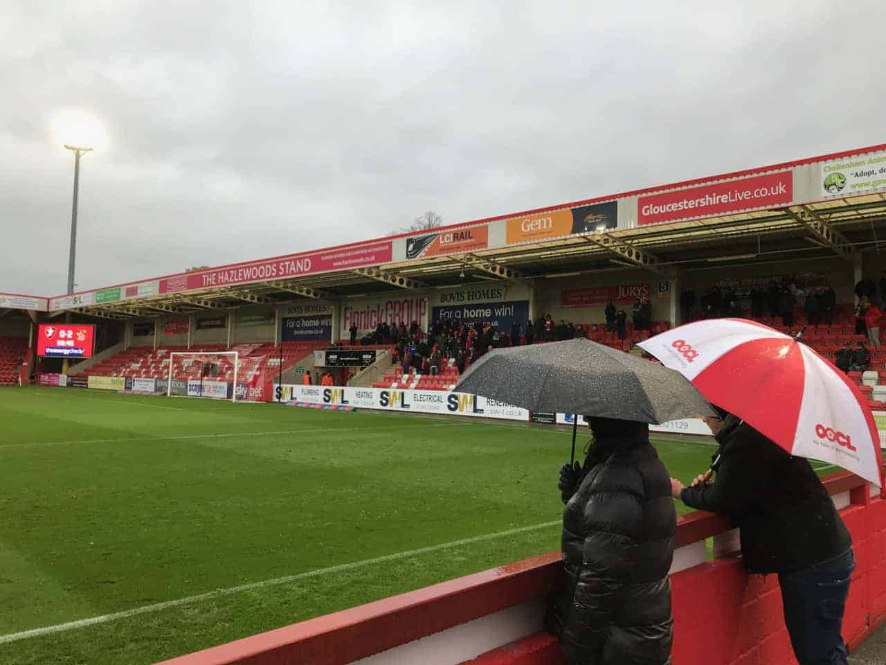 Supporters with umbrellas watching a game at Whaddon Road, home of Cheltenham Town FC.