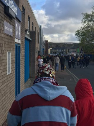Elderly supporter with a badge-covered hat at Turf Moor, home of Burnley Football Club