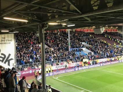 Chelsea fans in a stand behind the goal at Turf Moor, home of Burnley Football Club