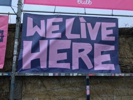 """Supporters' signs reading """"We Live Here"""" at Champion Hill, the home of Dulwich Hamlet FC in South London."""