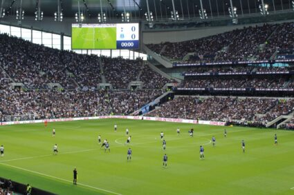 Players on the field in a full Tottenham Hotspur Stadium.