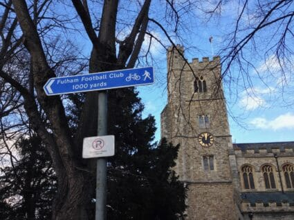 Sign near a church pointing to Fulham Football Club.