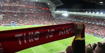 liverpool fan holding scarf in stands at anfield with view of pitch