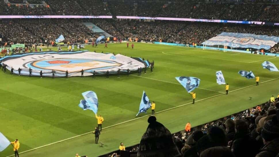people carrying manchester city flags and banner on field inside stadium
