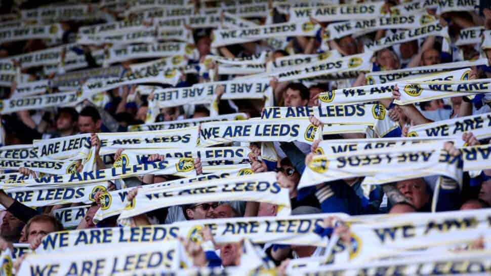 Premier League Leeds fans holding supporter scarves