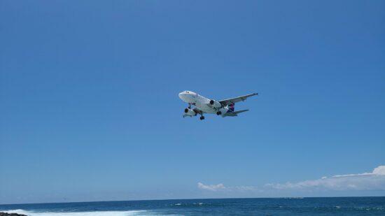 airplane landing over ocean