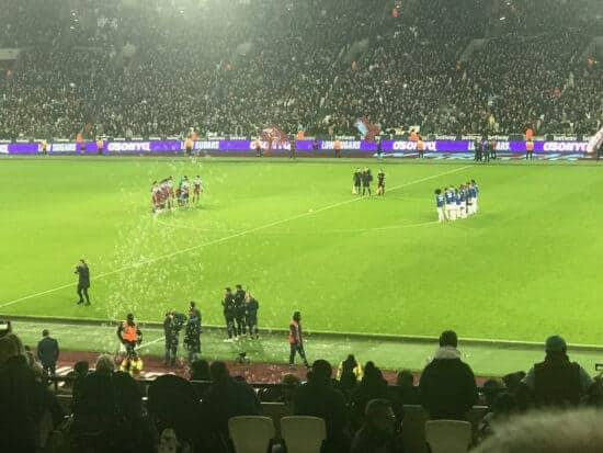 Players before kickoff on the pitch at West Ham United's London Stadium.