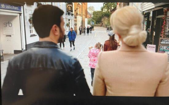 "Screen shot of ""Ted Lasso"" characters walking down a street in Twickenham, London."