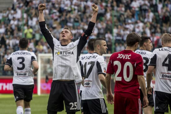 Legia Warsaw player celebrating with arms in air