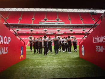 """screenshot from """"ted lasso"""" of soccer players on the sideline at Wembley Stadium"""