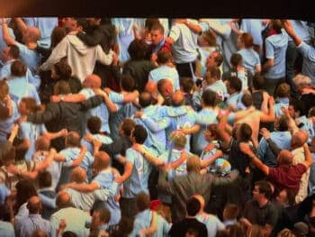 manchester city fans dancing with their back to the pitch