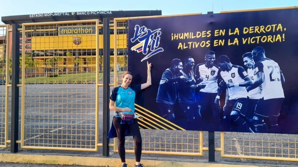 smiling female La Tri fan pointing at poster outside Estadio Monumental