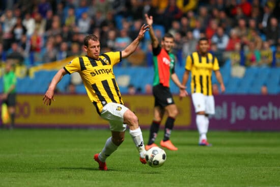 Vitesse player wearing black and yellow striped shirt white shorts
