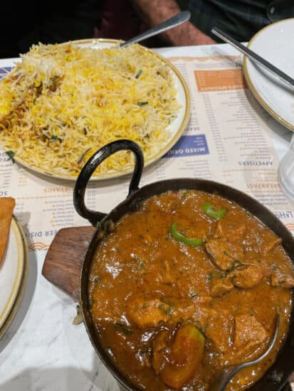 a plate of biryani and a bowl of stewed meat