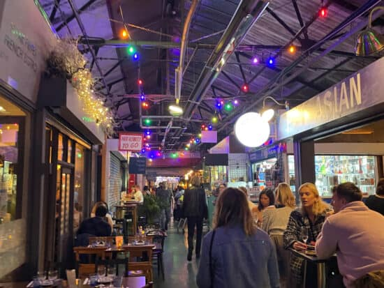 bar area with colorful lights inside broadway market in london