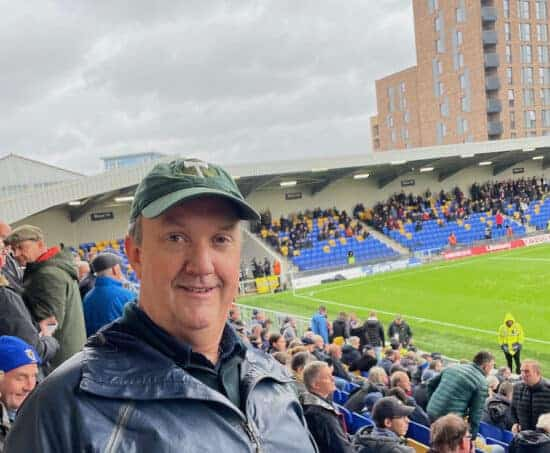 man with timbers cap at a football game